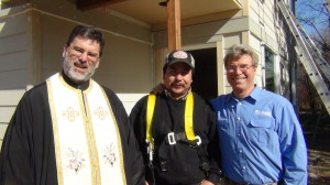 Father Michael Tervo of St. Sophia's Greek Orthodox Church, with Habitat partner Jaime Huante, and Habitat International Ambassador Steve Thomas on the site of Jaime's future home in Bellingham.