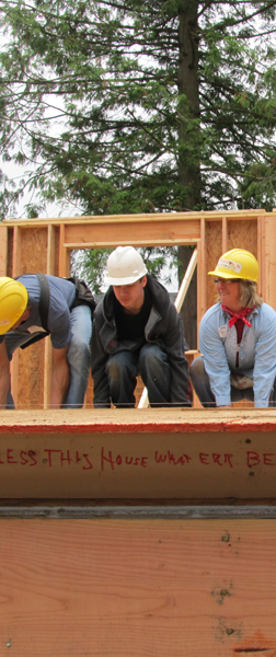 Habitat volunteers lift a wall.