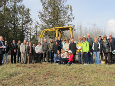 Volunteers and partner family members gather on the site of a future Habitat home.